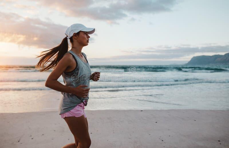 Jeune femme convenable pulsant à la plage dans le matin photographie stock libre de droits