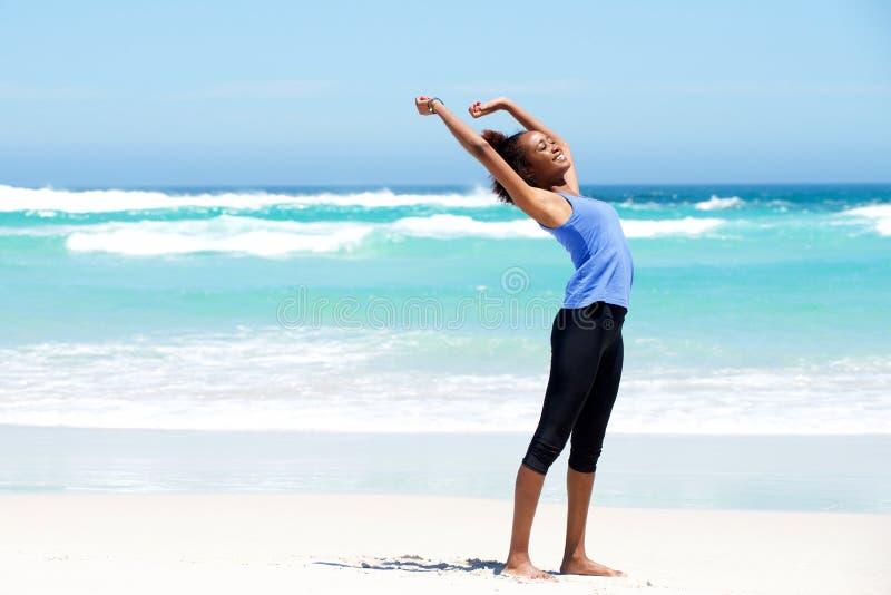 Jeune femme convenable s'étirant à la plage image stock