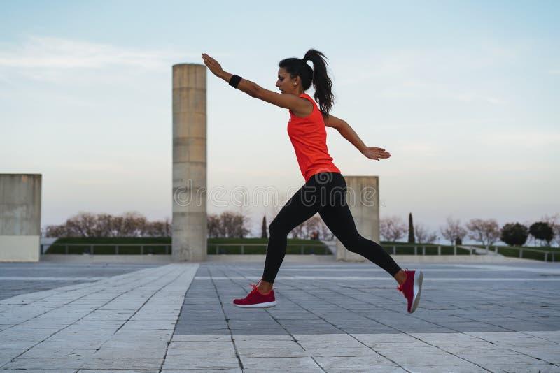 Jeune femme convenable sautant tout en courant Forme physique et mode de vie sain photo stock