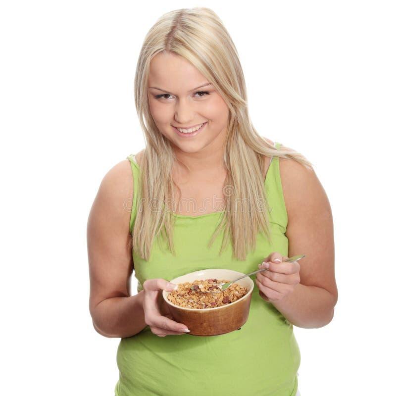 Jeune femme corpulent mangeant la mousseline photo stock