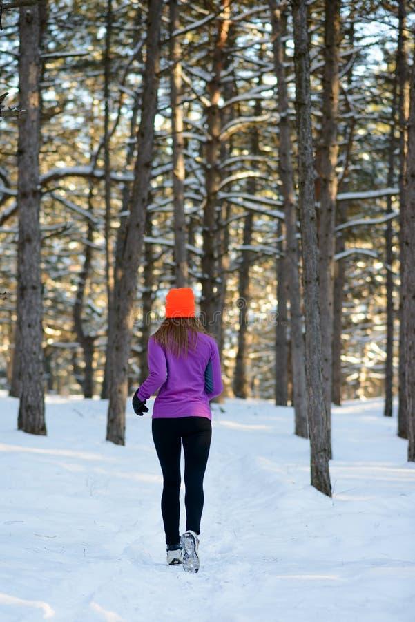 Jeune femme courant dans la belle forêt d'hiver chez Sunny Frosty Day Concept actif de style de vie photos libres de droits