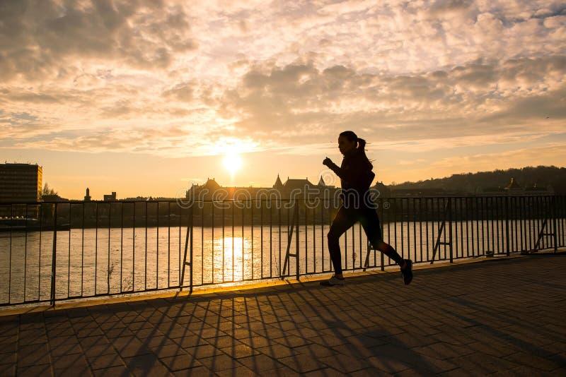 Jeune femme courant dans le coucher du soleil photos libres de droits