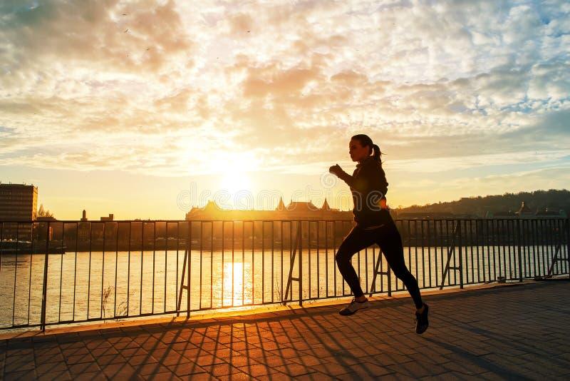Jeune femme courant dans le coucher du soleil photo libre de droits