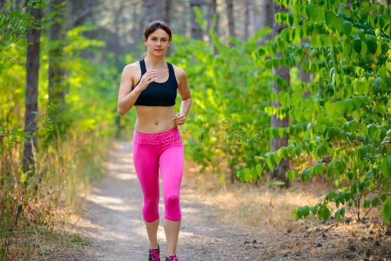 Jeune femme courant sur la traînée dans beau Forest Active Lifestyle Concept sauvage L'espace pour le texte images stock