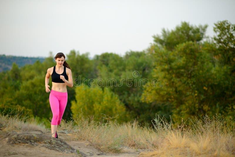 Jeune femme courant sur la traînée de montagne de matin Concept actif de style de vie photos stock