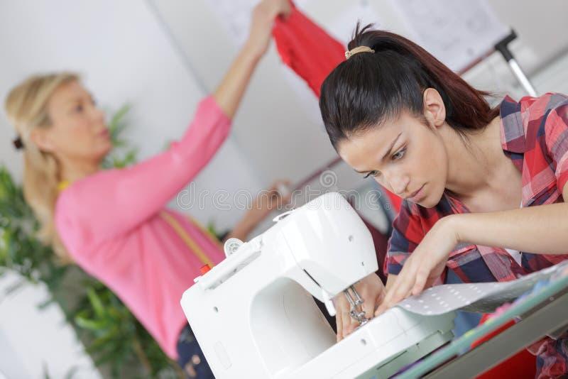 Jeune femme cousant avec la machine à coudre au lieu de travail photo stock