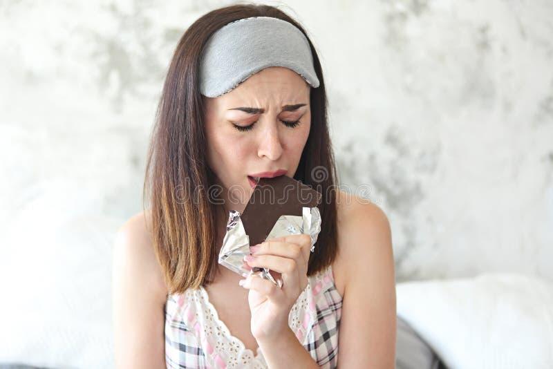 Jeune femme craing triste gaie mangeant la barre et la conservation de chocolat images libres de droits