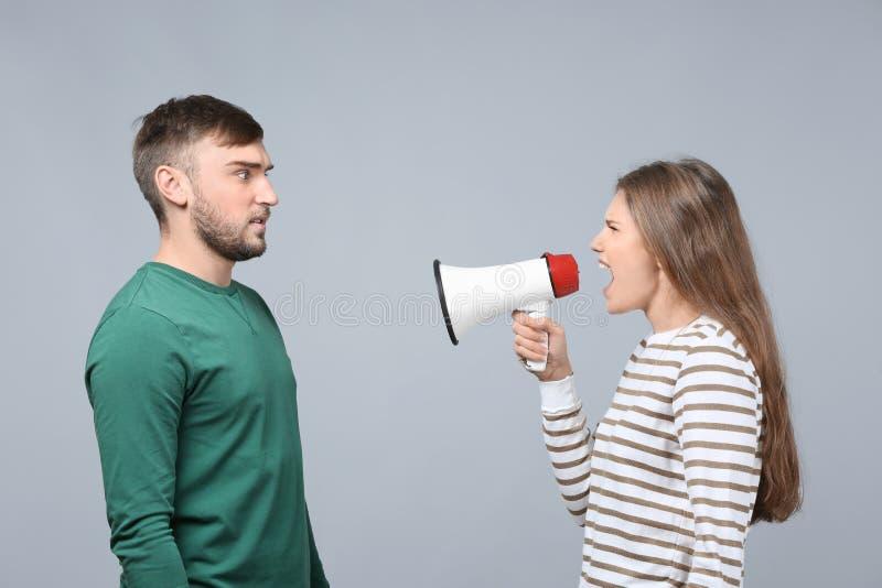Jeune femme criant dans le mégaphone à l'homme image stock