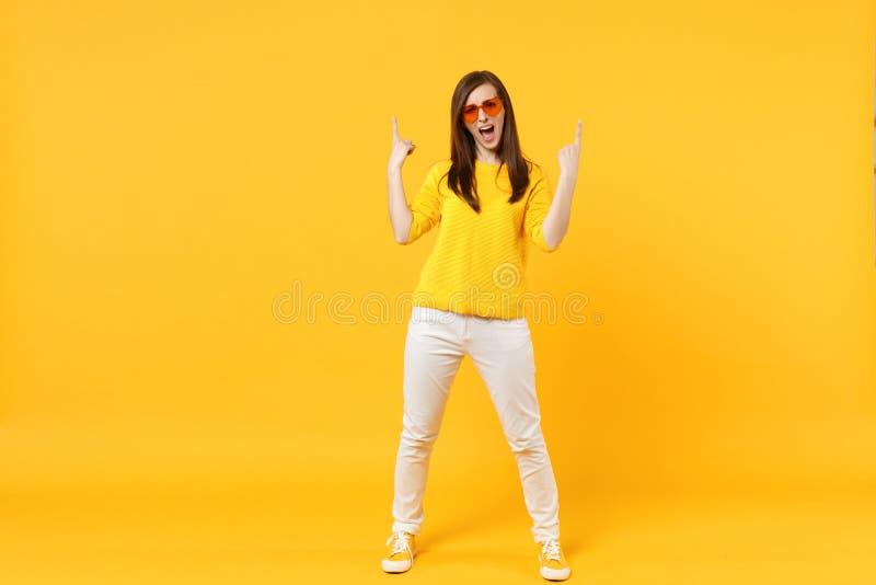 Jeune femme criarde dans des vêtements sport, verres de coeur dirigeant des index d'isolement sur le mur jaune-orange image stock