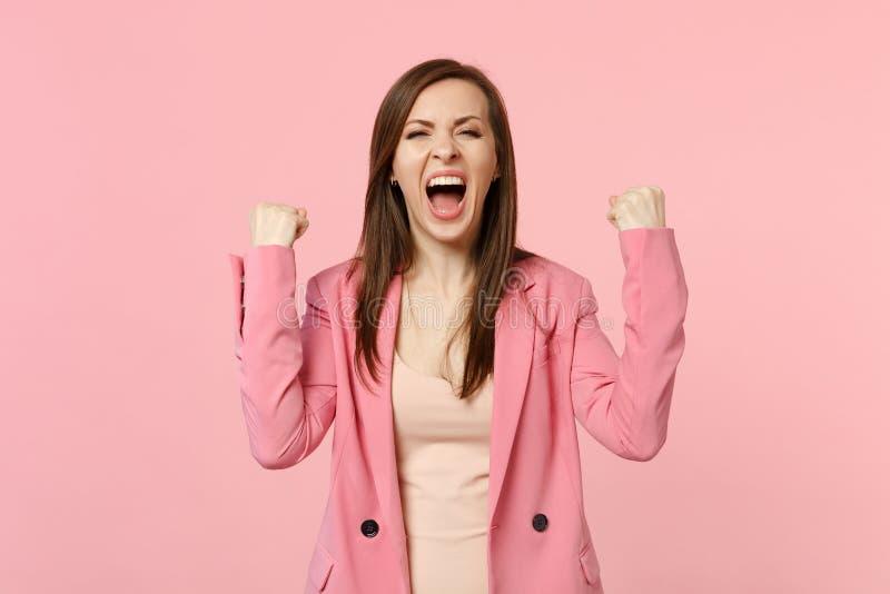 Jeune femme criarde heureuse dans des poings de serrage de veste comme gesticuler expressif de gagnant avec des mains d'isolement photos stock