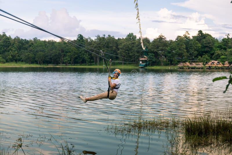 Jeune femme croisant un lac dans la ligne de fermeture éclair en Chiang Mai image libre de droits