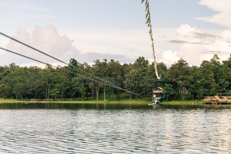 Jeune femme croisant un lac dans la ligne de fermeture éclair en Chiang Mai photographie stock libre de droits