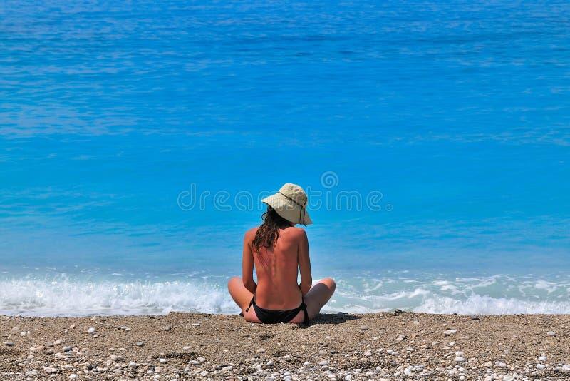 Jeune femme décolorée au soleil s'asseyant au bord de la mer photo stock