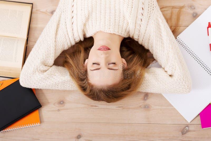 Jeune femme décontractée d'étudiant se trouvant sur le plancher photos stock