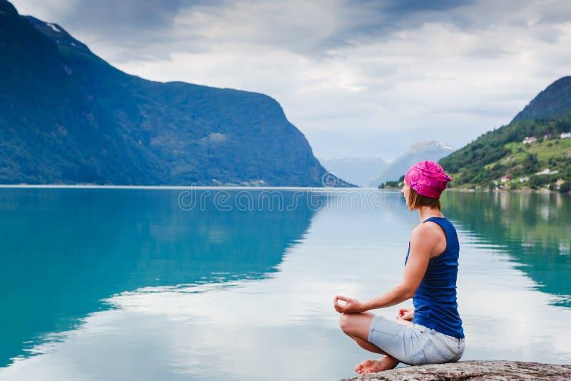 jeune femme décontractée de yoga dans la pose de yoga près du lac images libres de droits