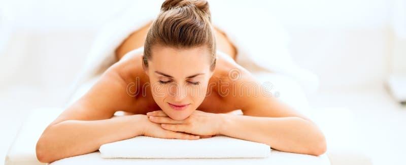 Jeune femme décontractée s'étendant sur la table de massage photos libres de droits