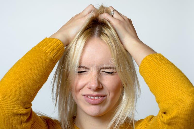 Jeune femme dégoûtée rayant sa tête photographie stock libre de droits
