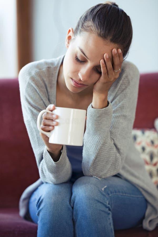 Jeune femme déprimée ayant le mal de tête tout en buvant du café sur le sofa à la maison photos libres de droits