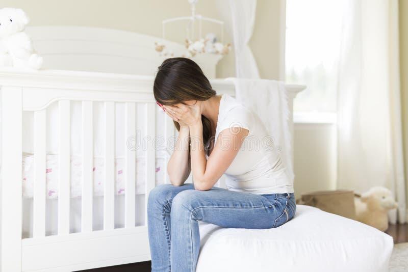 Jeune femme déprimée dans la chambre de bébé images stock