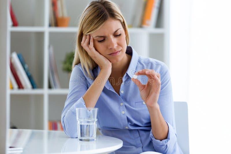 Jeune femme déprimée prenant des pilules à la maison image stock