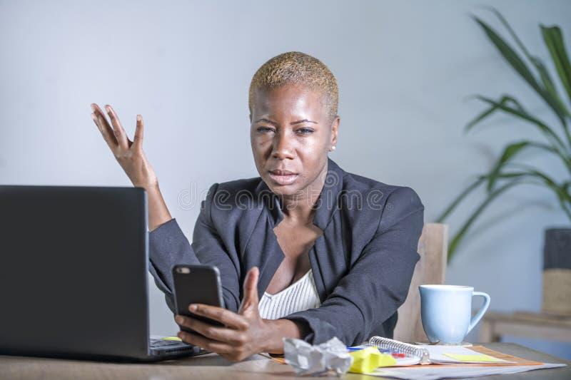 Jeune femme désespérée et soumise à une contrainte d'affaires d'afro-américain nous travaillant au bureau d'ordinateur portable a photo stock