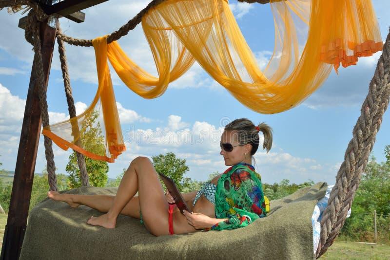 Jeune femme détendant dans l'hamac avec le comprimé photographie stock libre de droits