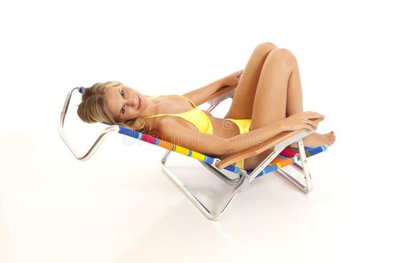 Jeune femme détendant dans la présidence de plage image libre de droits