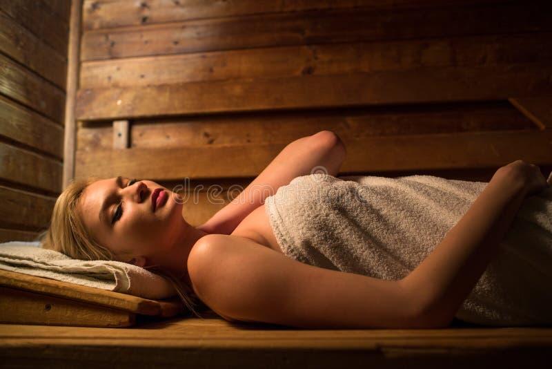 Jeune femme détendant dans un sauna photos stock