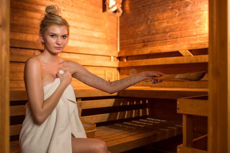 Jeune femme détendant dans un sauna image libre de droits