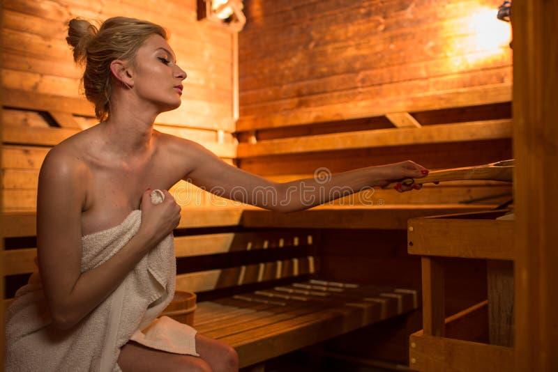 Jeune femme détendant dans un sauna image stock