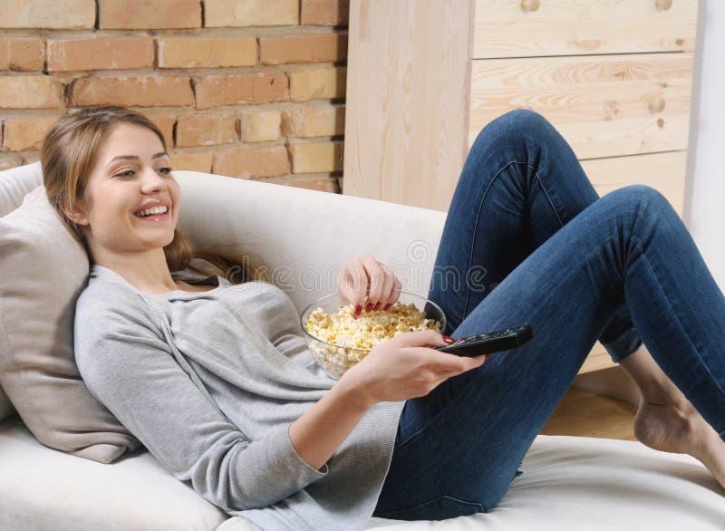 Jeune femme détendant et regardant la TV avec le maïs éclaté sur le sofa à images libres de droits