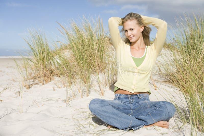 Jeune femme détendant parmi des dunes image stock