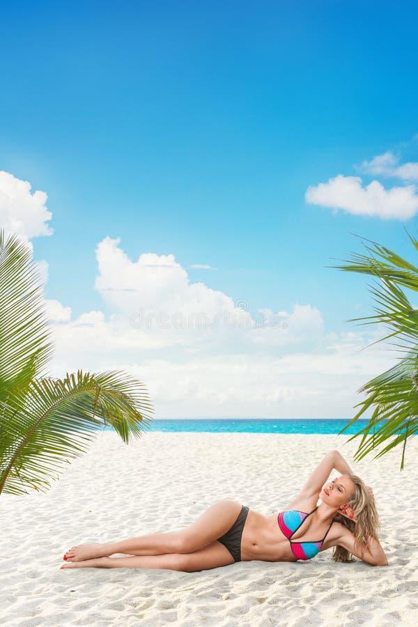 Jeune femme détendant sur la plage photo stock
