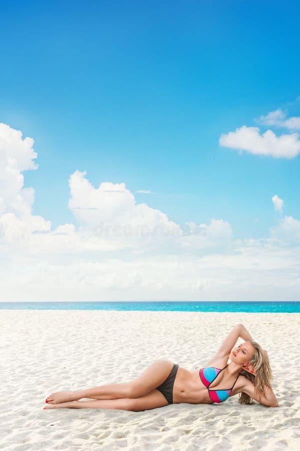 Jeune femme détendant sur la plage image stock