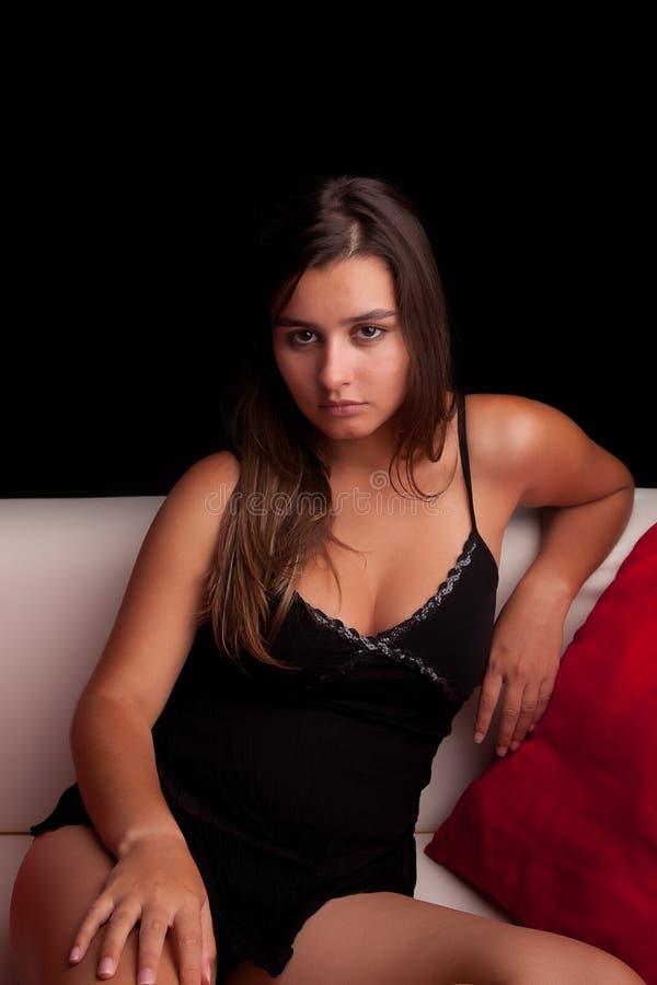 Jeune femme détendant sur le divan image libre de droits