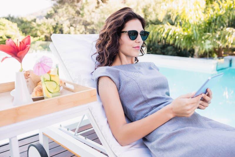 Jeune femme détendant sur un canapé du soleil près du poolside image libre de droits