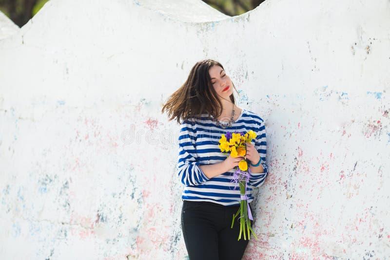 Jeune femme d'été dans le gilet dépouillé avec le bouquet vibrant des freesias jaunes et des iris près de mur de ciment photographie stock