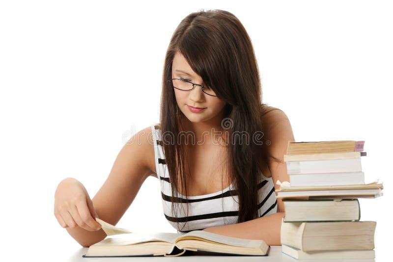 Jeune femme d'étudiant avec un bon nombre de livres studing. images libres de droits