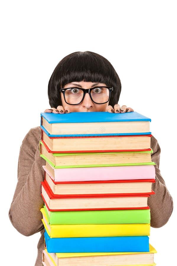 Jeune femme d'étudiant jetant un coup d'oeil de la pile de livres, d'isolement image stock
