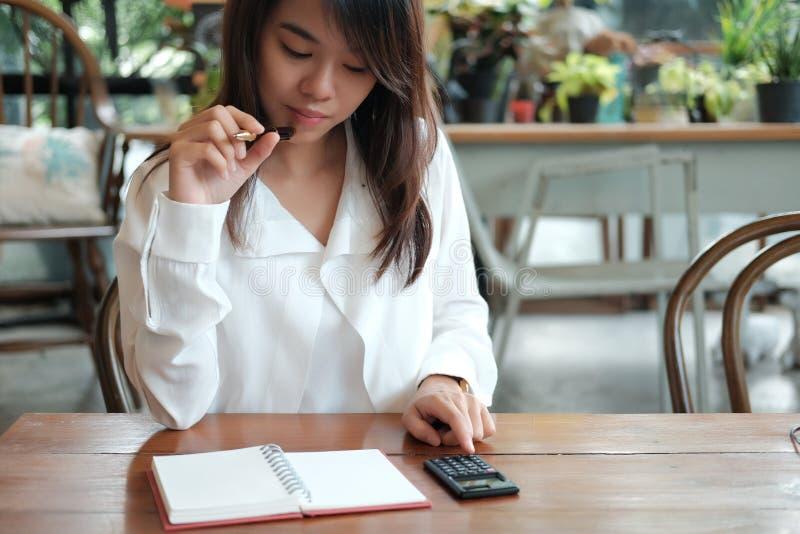 Jeune femme d'étudiant se tenant avec le stylo et pensant à quelque chose h photographie stock libre de droits