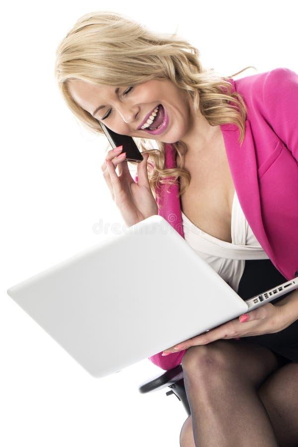 Jeune femme d'affaires à l'aide d'un ordinateur portable et d'un téléphone portable mobile photos stock