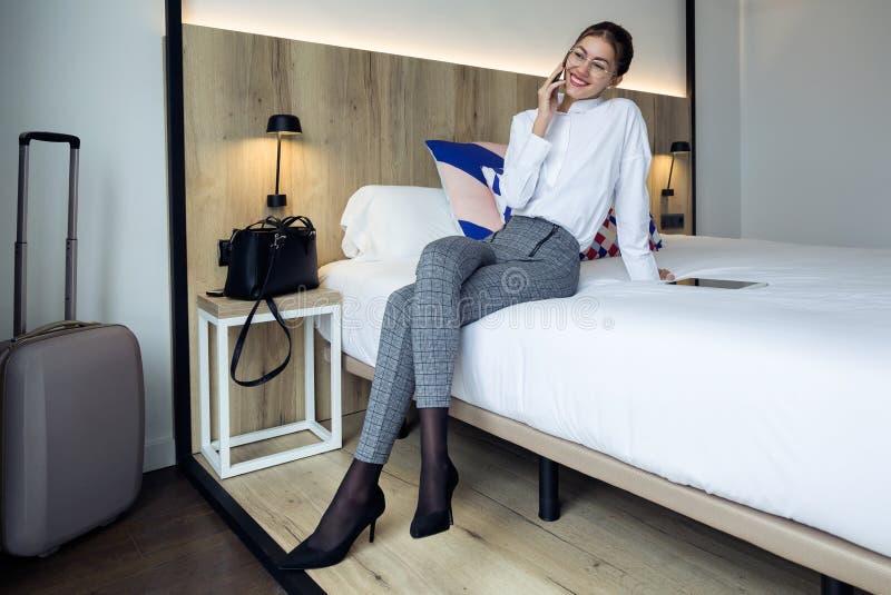 Jeune femme d'affaires élégante parlant avec son téléphone de Mobil se reposant sur le lit à la chambre d'hôtel images libres de droits