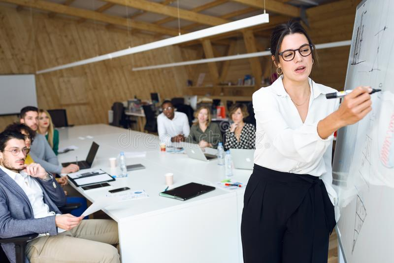 Jeune femme d'affaires élégante se dirigeant au tableau noir blanc et expliquer un projet à ses collègues sur l'endroit coworking image stock