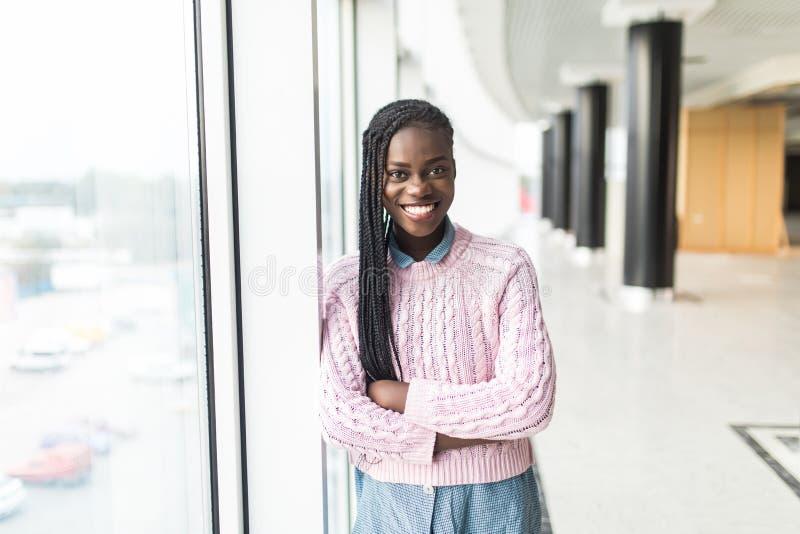 Jeune femme d'affaires africaine attirante regardant fixement pensivement par des fenêtres de bureau l'horizon de ville photos stock