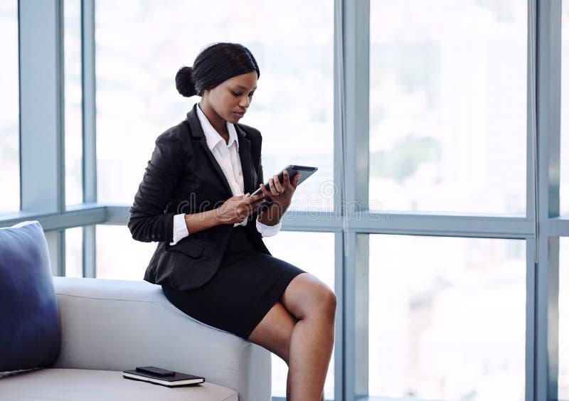 Jeune femme d'affaires africaine regardant l'écran sur son comprimé images stock