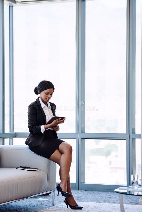 Jeune femme d'affaires africaine regardant l'écran sur son comprimé photo libre de droits