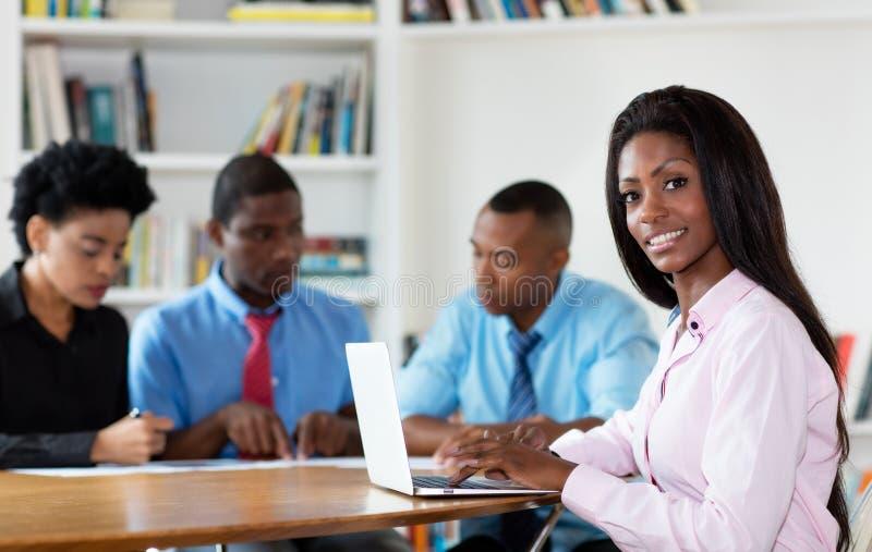 Jeune femme d'affaires d'afro-américain avec l'équipe et l'ordinateur photos stock