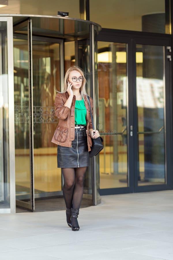 Jeune femme d'affaires américaine parlant au téléphone en dehors de l'immeuble de bureaux photo stock