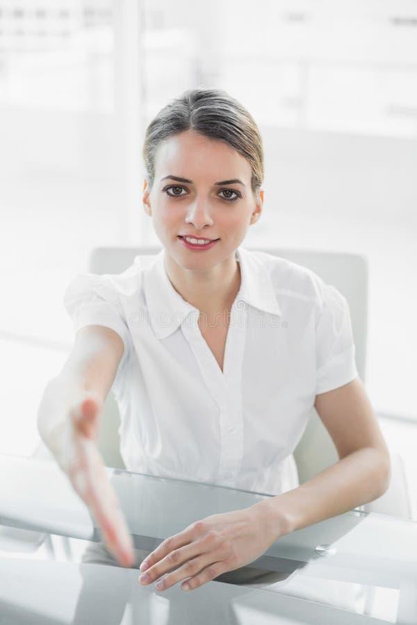 Jeune femme d'affaires amicale atteignant sa main à l'appareil-photo image libre de droits
