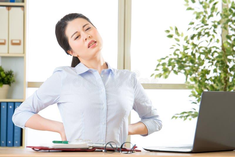 Jeune femme d'affaires asiatique avec de douleur le dos dedans images stock
